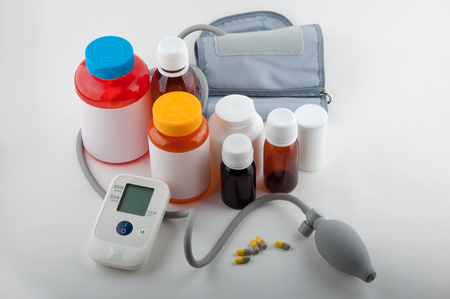 preasure: Blood preasure tonometer, yellow and grey capsules, colorful bottles for tablets on white background