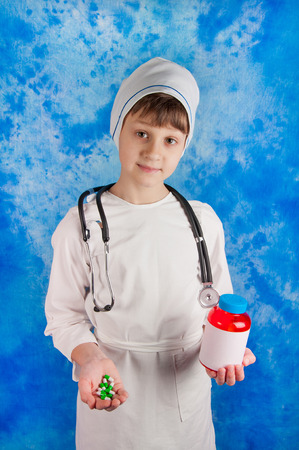 stethoscope boy: Young boy in white medicine costume and stethoscope holding pills and bottle in his hands