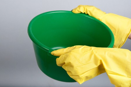 washbowl: Human hands in yellow rubber gloves hold green washbowl
