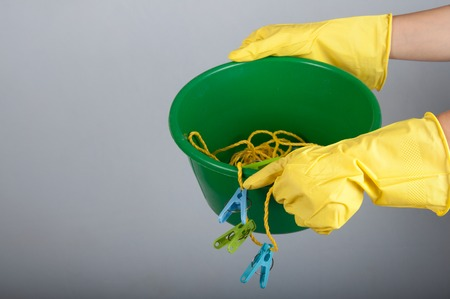 washbowl: Human hands in rubber gloves hold washbowl with clotheslines and clothespins