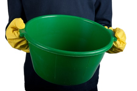 washbowl: Human in dark-blue shirt and rubber gloves holds small green washbowl. Isolated on white