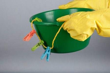 washbowl: Hands in yellow rubber gloves hold small green washbowl with colored clothespins and clothline
