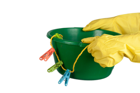 washbowl: Hands in yellow gloves hold washbowl with clothespins and clothesline. Isolated on white Stock Photo