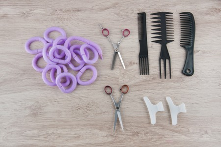 hairdressing accessories: Professional hairdressing accessories. Purple curlers, comb, brushes, purple curlers and hair spins laying on wooden table