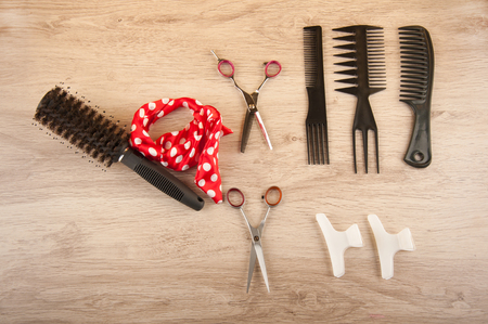 hairdressing accessories: Salon hairdressing accessories laying on wooden table. Black comb, brush, scissors, white spins and red ribbon