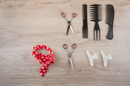 hairdressing accessories: Professional salon hairdressing accessories laying on wooden table. Black comb, brush, scissors, white spins and red ribbon. Space for text. Stock Photo