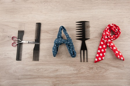 hairdressing accessories: Word hair consist of hairdressing accessories laying on wooden table. Comb, Brush, scissors and colored ribbons