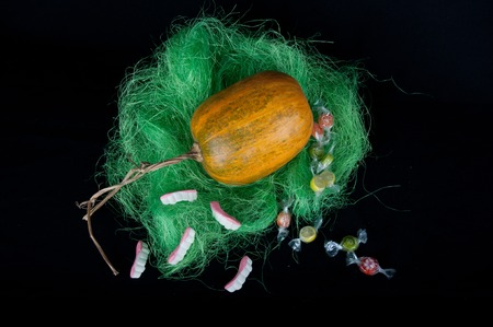 pasto sintetico: De calabaza naranja en hierba sintética verde con los dulces redondos y dulces en forma de los dientes que se sobre fondo negro