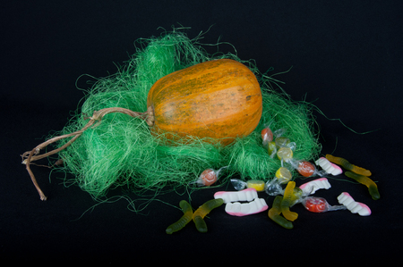 pasto sintetico: Halloween decoration. Big orange pumpkin in green grass and different form sweets on black background