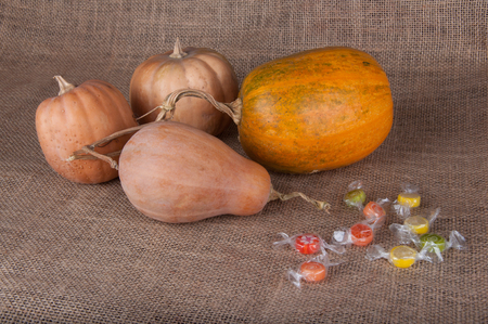 multycolored: Four pumpkins and multycolored round sweets laying on beige sackcloth Stock Photo