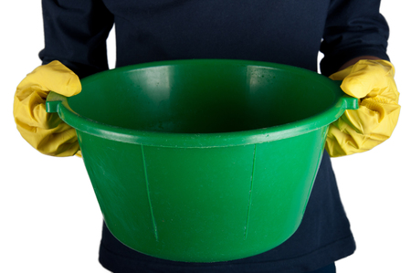 washbowl: Human in dark-blue shirt and yellow rubber gloves holds small green washbowl. Isolated on white