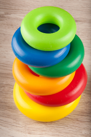 Pyramid of different size and color toy plastic rings on wooden table Stock Photo - 72094046