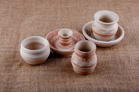chatty: Ceramic goods. Three greybeards, dish and candlestick with patterns on brown sackcloth background Stock Photo