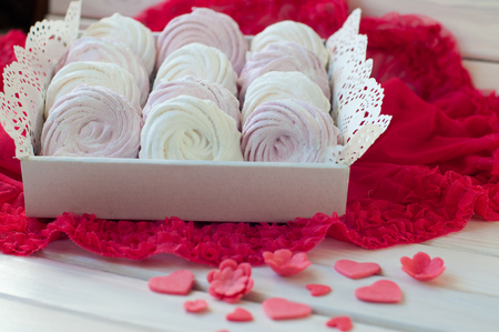 Composition of white and rose zephyr in box lay on red fabric, white wooden table near small sweet flower, heart figures Stock Photo