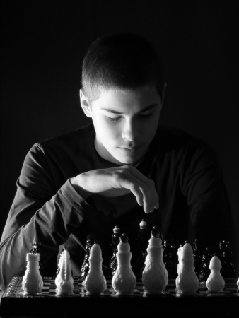 Teenage boy looking at the chessboard photo