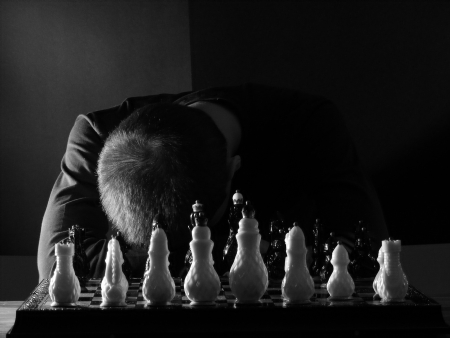 slumped: Teenage boy slumped over the chess board in desperation