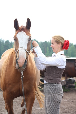 Beautiful young blonde woman getting chestnut horse ready for the riding photo