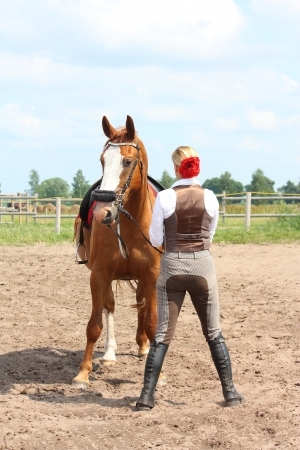 Beautiful young blonde woman and chestnut horse looking at each other photo