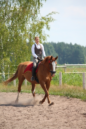 Beautiful young blonde woman riding trotting chestnut horse Stock Photo - 16336511