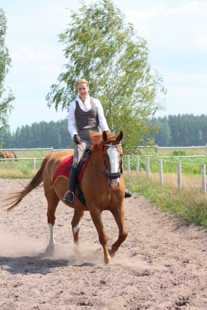 Beautiful young blonde woman riding trotting chestnut horse Stock Photo - 16336514