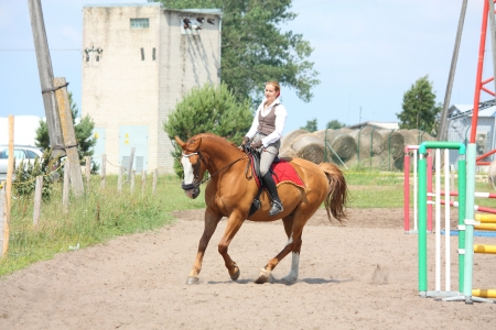 trotting: Beautiful young blonde woman riding trotting chestnut horse Stock Photo