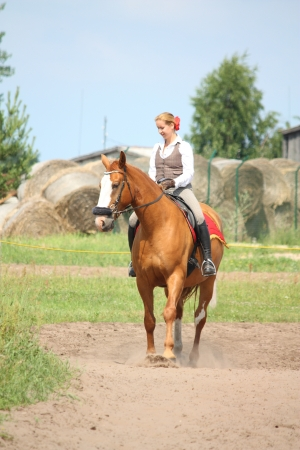Beautiful young blonde woman riding trotting chestnut horse photo