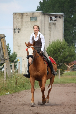 Beautiful young blonde woman riding trotting chestnut horse Stock Photo - 16380758