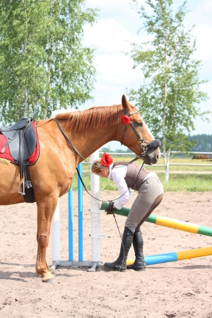 Beautiful young blonde woman setting the barrier for show jumping it with chestnut horse photo