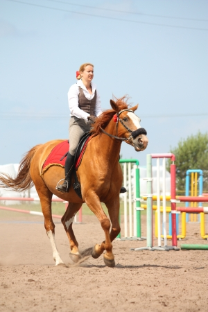 Beautiful young blonde woman riding cantering chestnut horse photo
