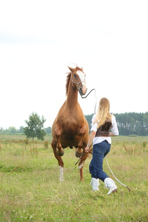 Young blonde woman commanding horse to rear (stand up) Stock Photo - 16380727