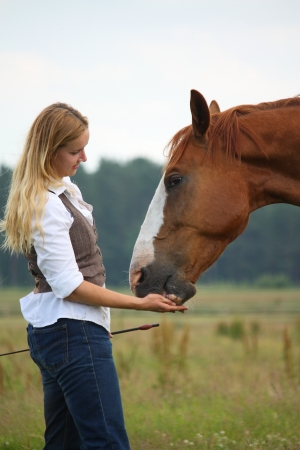 Woman giving horse a treat for a good job photo