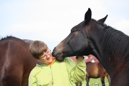 Smiling teenager boy with horses at the flower field in summer photo