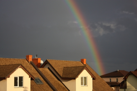 Rainbow over the cottage roof in rural area photo
