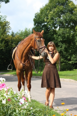 Beautiful girl in brown dress and chestnut horse portrait near the blooming flower bed Stock Photo - 19505213