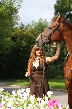 Beautiful girl in brown dress and chestnut horse portrait near the blooming flower bed photo