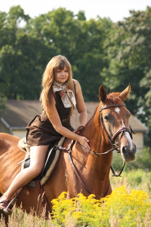 Beautiful teenager girl riding brown horse at the field of flowers photo
