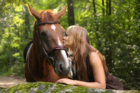 Beautiful girl and brown horse portrait in mysterious forest in summer photo