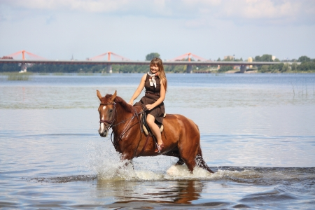 Beautiful teenage girl riding horse in the river in summer photo
