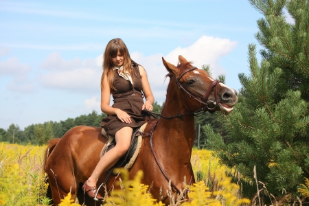 Beautiful teenager girl riding brown horse at the field of flowers