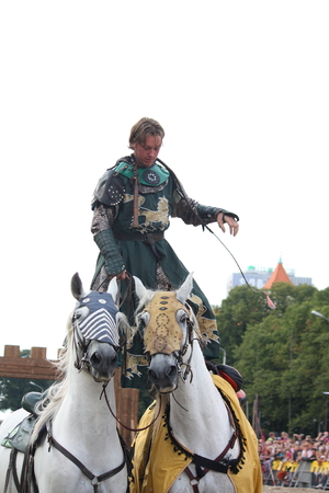 RIGA, LATVIA - AUGUST 21: Unidentified man from The Devils Horsemen stunt team standing on two galloping white horses during Riga Festival on August 21, 2011 in Riga, Latvia