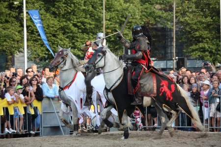 RIGA, LATVIA - AUGUST 21: Two members of The Devils Horsemen stunt team riding horses and fighting with swords during Riga Festival on August 21, 2011 in Riga, Latvia