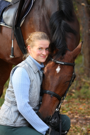 Beautiful blonde woman and brown horse in autumn photo
