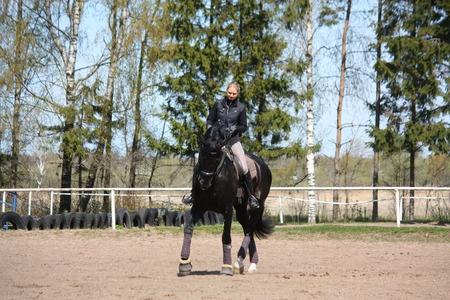Blonde woman riding black sport horse photo