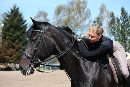 gelding: Portrait of blonde woman riding black horse
