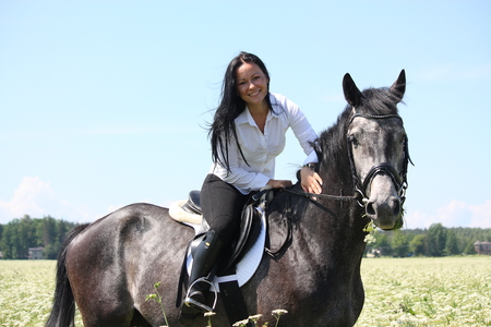gelding: Beautiful young woman riding gray horse at the blooming field in summer Stock Photo