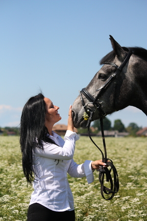 gelding: Beautiful caucasian young woman and horse portrait at the field with flowers Stock Photo