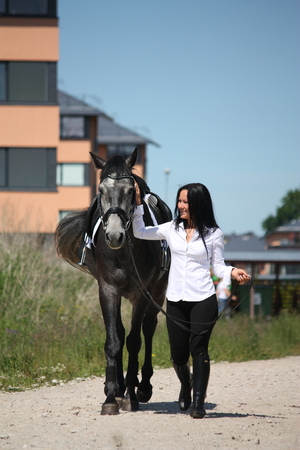 gelding: Beautiful caucasian young woman and gray horse walking