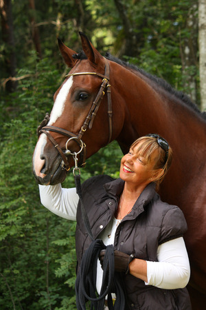 Happy elderly caucasian woman and bay latvian horse portrait in forest Stock Photo