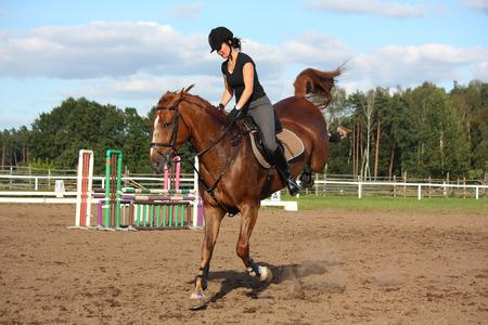 Brunette woman riding playful bucking chestnut horse Stok Fotoğraf