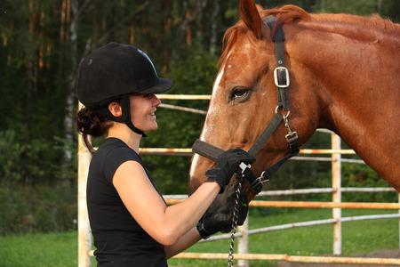 riding helmet: Mujer en casco de equitaci�n y Retrato del caballo marr�n en verano